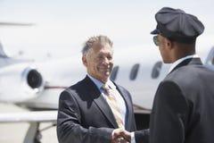 Fondo di And Aircraft In del pilota di Shaking Hands With dell'uomo d'affari immagine stock libera da diritti