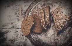 Fondo di concetto del forno Intera pane e coltello affettati del grano segale Fotografia Stock