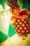 Fondo di estate con il cocktail e l'ananas con gli occhiali da sole Fotografia Stock