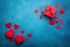Fondo di festa con il contenitore di regalo e cuori rossi sulla vista blu del piano d'appoggio Scheda di giorno dei biglietti di  Fotografie Stock