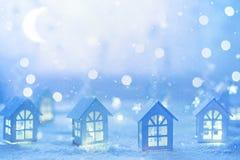 Fondo di festa con le piccole case e ghirlande di legno della stella Immagine Stock