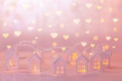 Fondo di festa con le piccole case di legno e le ghirlande calorose Fotografie Stock Libere da Diritti