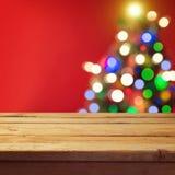 Fondo di festa di Natale con la tavola di legno vuota della piattaforma sopra il bokeh dell'albero di Natale Aspetti per il monta Immagine Stock