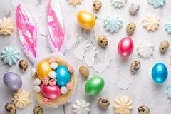 Fondo di festa di Pasqua Uovo di Pasqua con le orecchie su un fondo leggero, con i dolci Composizione orizzontale struttura per immagini stock