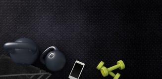 Fondo di forma fisica con i kettlebells e lo smartphone Fotografie Stock