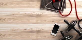 Fondo di forma fisica con le teste di legno e lo smartphone Vista da sopra Immagine Stock