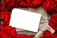 Fondo di giorno di biglietti di S cartolina d'auguri in bianco nel telaio fatto dei fiori delle rose rosse e del contenitore di r Fotografia Stock
