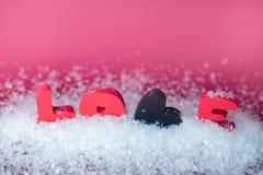 Fondo di giorno di biglietti di S Testo di amore in neve su fondo rosa fotografia stock