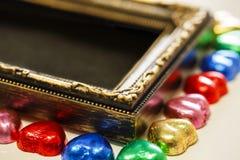 Fondo di giorno di biglietti di S. Valentino con forma variopinta del cuore del cioccolato e struttura dell'oro dalla vista super Fotografia Stock