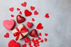 Fondo di giorno di biglietti di S. Valentino con il contenitore di regalo ed i cuori rossi fotografia stock