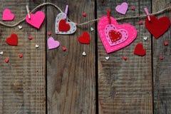 Fondo di giorno del ` s del biglietto di S. Valentino con i cuori fatti a mano del feltro, mollette da bucato Regalo che fa, hobb Fotografia Stock