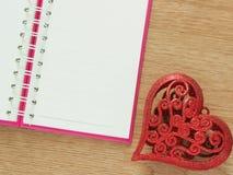 Fondo di giorno di biglietti di S. Valentino con il cuore rosso di scintillio e libro per il diario sul pavimento di legno Amore  Immagini Stock