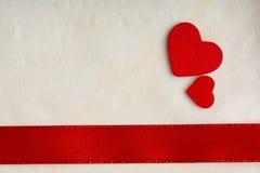 Fondo di giorno di biglietti di S. Valentino. Nastro e cuori rossi del raso. Immagine Stock