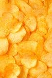 Fondo di grandi fette dei chip ondulati ondulati dorati con il mare Fotografie Stock Libere da Diritti