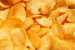 Fondo di grandi fette dei chip ondulati ondulati dorati con il mare Fotografia Stock