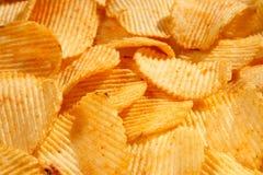 Fondo di grandi fette dei chip ondulati ondulati dorati con il mare Fotografia Stock Libera da Diritti