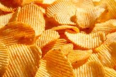 Fondo di grandi fette dei chip ondulati ondulati dorati con il mare Immagine Stock Libera da Diritti