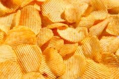 Fondo di grandi fette dei chip ondulati ondulati dorati con il mare Immagine Stock