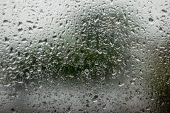 Fondo di immagine di sfuocatura di goccia di acqua sulla finestra di automobile e sul fondo della via Fotografia Stock Libera da Diritti