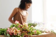Fondo di lavoro del bello fiorista femminile africano Fuoco sui alstroemerias Immagini Stock