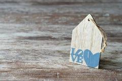 Fondo di legno accogliente, con un pezzo di legno sotto forma di una casa, di un cuore e della parola scritti amore, concetto di  fotografia stock