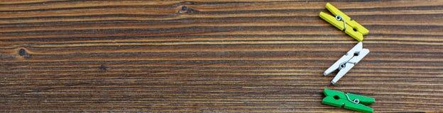 Fondo di legno con le mollette da bucato colorate Insegna per il sito Web Immagine Stock