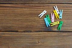 Fondo di legno con le mollette da bucato colorate Posto per testo top Fotografie Stock