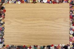 Fondo di legno con un confine variopinto del bottone Immagini Stock