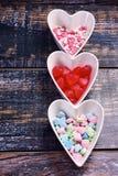 Fondo di legno del biglietto di S. Valentino con le ciotole a forma di del cuore Immagine Stock
