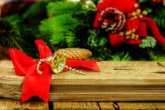 Fondo di legno di Natale rustico con la campana rossa dell'oro e dell'arco Fotografia Stock Libera da Diritti