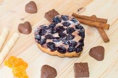 Fondo di legno ed accanto ad una caramella dei bastoni t di forma e di cannella del cuore del cioccolato Immagine Stock Libera da Diritti