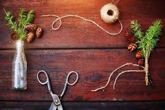Fondo di legno di Natale Rami e coni attillati in bottiglia d'annata, vecchie forbici e cavo astuto Il concetto del traini Fotografia Stock Libera da Diritti