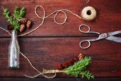 Fondo di legno di Natale Rami e coni attillati in bottiglia d'annata, vecchie forbici e cavo astuto Il concetto del traini Immagini Stock Libere da Diritti