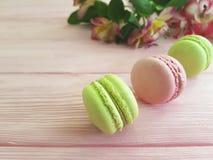 Fondo di legno rosa dolce variopinto di Macaron, foglia del fiore di alstroemeria del biscotto del pranzo Immagine Stock Libera da Diritti