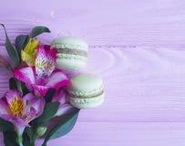 Fondo di legno rosa variopinto di Macaron, foglia del fiore di alstroemeria del biscotto Immagine Stock