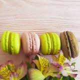 Fondo di legno rosa variopinto di Macaron, foglia del fiore di alstroemeria del biscotto del pranzo Immagine Stock
