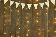 Fondo di legno scuro con le luci e le bandiere, contesto astratto di festa, spazio della copia per testo Immagine Stock