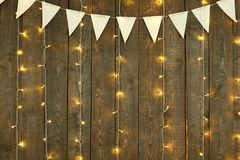 Fondo di legno scuro con le luci e le bandiere, contesto astratto di festa, spazio della copia per testo Immagini Stock Libere da Diritti