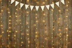 Fondo di legno scuro con le luci e le bandiere, contesto astratto di festa, spazio della copia per testo fotografie stock