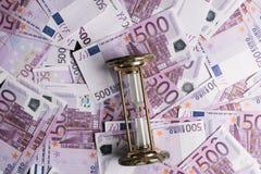 fondo di molte 500 euro banconote con la clessidra Valuta di UE Fotografie Stock Libere da Diritti