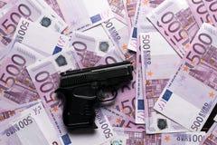 fondo di molte 500 euro banconote con la pistola Valuta di UE Fotografia Stock Libera da Diritti