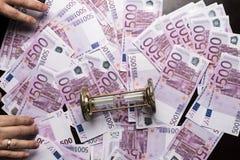 fondo di molte 500 euro banconote con le mani degli uomini e della clessidra Valuta di UE Fotografia Stock