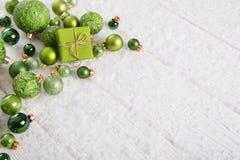 Fondo di natale bianco e di verde con il contenitore di regalo, la neve ed il bal Immagine Stock