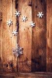 Fondo di Natale con gli ornamenti ed i fiocchi di neve festivi su ol Fotografie Stock