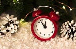 Fondo di Natale con i coni rossi dei fiocchi di neve della sveglia ed i coni Fotografia Stock
