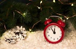 Fondo di Natale con i coni rossi dei fiocchi di neve della sveglia ed i coni Immagine Stock