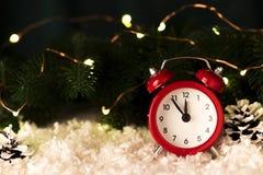 Fondo di Natale con i coni rossi dei fiocchi di neve della sveglia ed i coni Immagini Stock