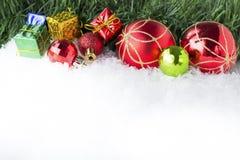 Fondo di Natale con i contenitori e le palle di regalo su neve Immagine Stock Libera da Diritti