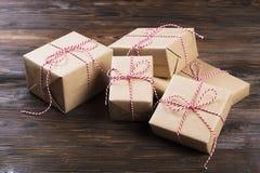Fondo di Natale con i contenitori di regalo del mestiere su fondo di legno Immagine Stock