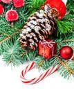 Fondo di Natale con i rami di albero dell'abete, le bagattelle rosse ed il gi Fotografia Stock